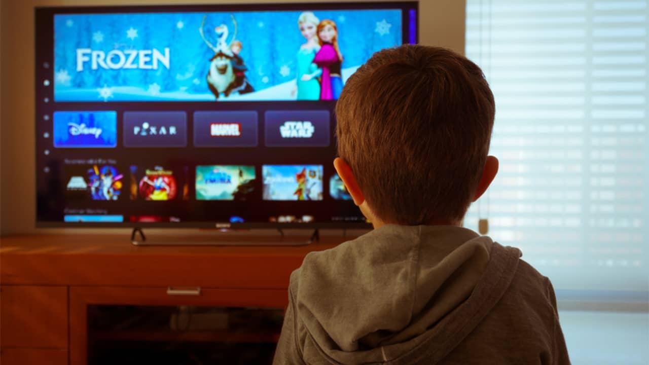 Un petit garçon qui regarde Disney+ sur une télévision