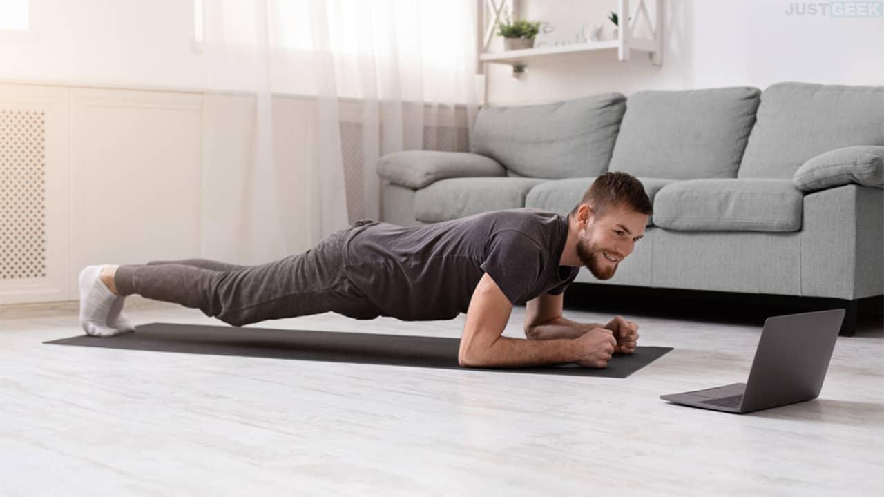 Un jeune homme qui pratique le sport à la maison devant son ordinateur