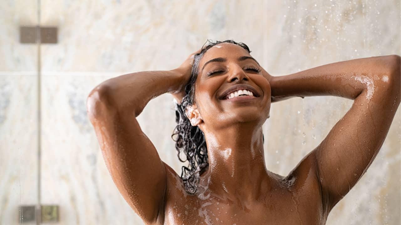 Femme qui se lave les cheveux dans sa douche